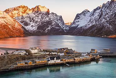 Rorbuer fishermen's huts on the island, at back sun lit mountains, Sakrisøya, Reine, Lofoten, Norway, Europe