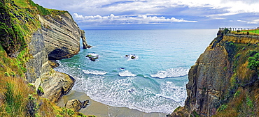 Steep cliff with arch of rock and small sandy beach, Cape Farewell, Tasman Sea, Puponga, North Island, New Zealand, Oceania