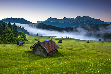 Small cabin on mountain meadow at forest edge, Geroldsee in the background Karwendel Mountains at sunrise, Kaltenbrunn, Upper Bavaria, Germany, Europe