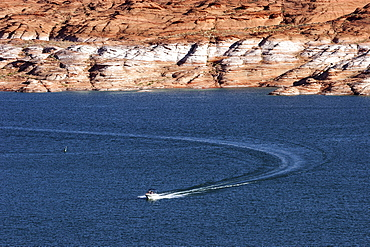 Boat on Lake Powell, red Navajo Sandstone cliffs behind, Page, Arizona, USA, North America