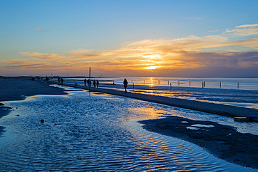 Beach walkers at the Wadden Sea on the North Sea coast in the blue hour at sunset, Norddeich, Lower Saxony, Germany, Europe