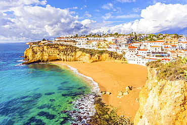 Wide sandy beach, white houses, cloudy sky, Carvoeiro, Algarve, Portugal, Europe