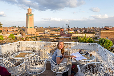 Young woman on a roof terrace reads the menu in the restaurant, view of the old town, mosque with minaret, evening mood, Marrakech, Morocco, Africa