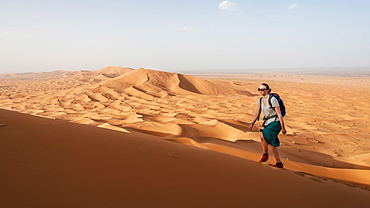Female hiker is running on a red sand dune in the desert, dune landscape Erg Chebbi, Merzouga, Sahara, Morocco, Africa
