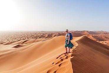 Female hiker on a red sand dune in the desert, dune landscape Erg Chebbi, Merzouga, Sahara, Morocco, Africa - 832-382275