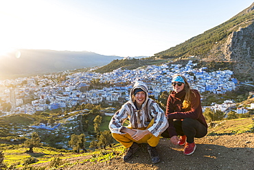 Young couple in Moroccan djellaba at lookout point, view on the medina of Chefchaouen, Chaouen, Tangier-Tétouan, Morocco, Africa