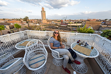 Young woman on a roof terrace, restaurant, view of the old city, mosque with minaret, Marrakech, Morocco, Africa