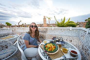 Young woman on a roof terrace in the restaurant, Moroccan food, tagine, view of the old town, mosque with minaret, evening mood, Marrakech, Morocco, Africa