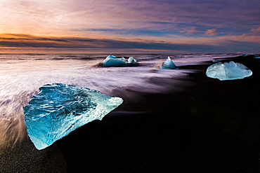 Chunks of ice on black lava sand beach at sunrise, lake Jokulsarlon, Vik, Iceland, Europe