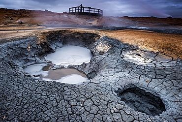 Solfataras, fumaroles, mud pots, sulfur and other minerals, a woman on the viewing platform at the back, high-temperature geothermal area or Hverarond or Hverir, Namafjall mountains, Myvatn area, Norourland eystra, Iceland, Europe
