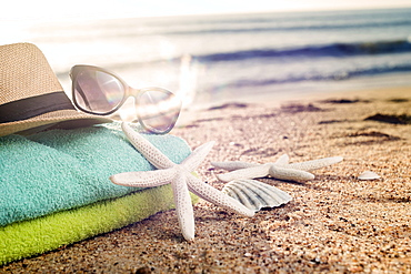 Summer accessories as colorful towels, straw hat, sun glasses and shells on the sandy beach