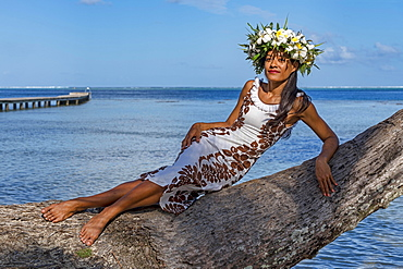 Young woman with flower wreath from Frangipani leaning on palm trunk, Raiatea, French Polynesia, Oceania