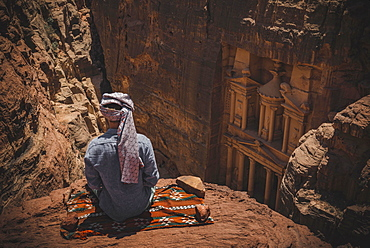 Tourist with turban sits on carpet and looks from above into the canyon Siq, Pharaoh's treasure house beaten into rock, facade of the treasure house Al-Khazneh, Khazne Faraun, mausoleum in the Nabataean city Petra, near Wadi Musa, Jordan, Asia