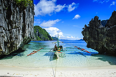 Outrigger boat on a little white beach and crystal clear water in the Bacuit archipelago, Palawan, Philippines, Asia