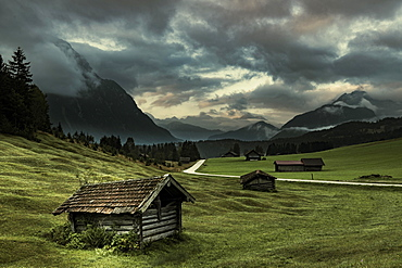 Small huts on mountain meadow with dramatic cloud sky and Wetterstein mountains in the background, Mittenwald, Bavaria, Germany, Europe