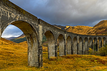 Glenfinnan railway viaduct, with autumn colours and cloudy sky, Glenfinnan, West Highlands, Scotland, Great Britain
