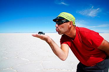 Optical illusion, man holds off-roader on hand, Salar de Uyuni, Uyuni, Potosi, Bolivia, South America