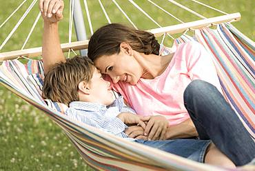 Mother and son lying in hammock, cuddling, Germany, Europe