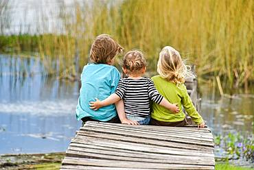 Three toddlers sitting together on an old jetty, back view, Patagonia, Argentina, South America