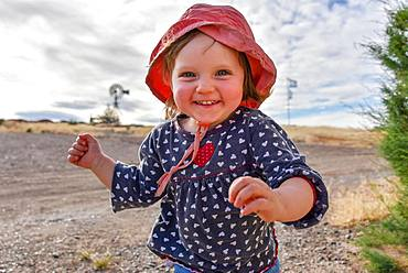 Little girl with red hat running and laughing, Patagonia, Argentina, South America