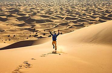 Young man walking down a sand dune, dune landscape Erg Chebbi, Merzouga, Sahara, Morocco, Africa