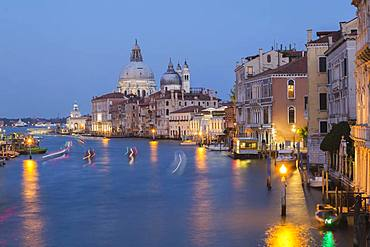 Grand Canal with light trails from water taxis, vaporettos in movement plus Renaissance architectural style palace buildings and Santa Maria della Salute basilica in Dorsoduro at dusk, Venice, Veneto, Italy, Europe