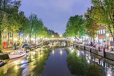 Canal with boats, bicycles on the street at night, Amsterdam, Holland, Netherlands