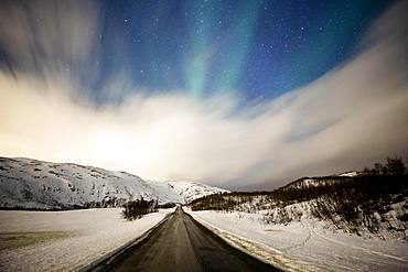 Northern lights over road with snow mountains, near Tromsoe, Troms, Norway, Europe