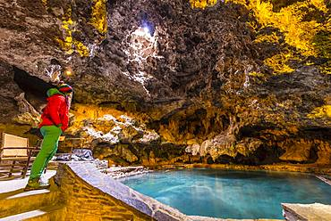 Young woman in a cave with a geothermal spring, Cave and Basin National Historic Site, Banff National Park, Alberta, Canada, North America