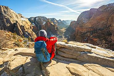 Young woman looking into the distance from Angels Landing to Zion Canyon, Angels Landing Trail, in winter, mountain landscape, Zion National Park, Utah, USA, North America