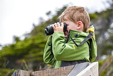 Interested boy looking through binoculars, Punta Arenas, Patagonia, Chile, South America