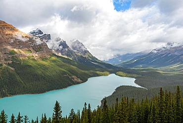 Clouds hanging in mountain peaks, turquoise glacial lake surrounded by forest, Peyto Lake, Rocky Mountains, Banff National Park, Alberta Province, Canada, North America