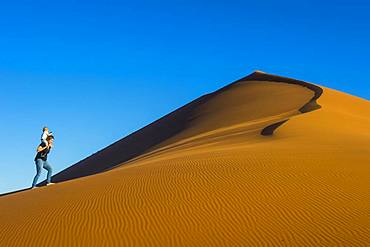 Woman with her baby walking up the giant sanddune Dune 45, Namib-Naukluft National Park, Namibia, Africa
