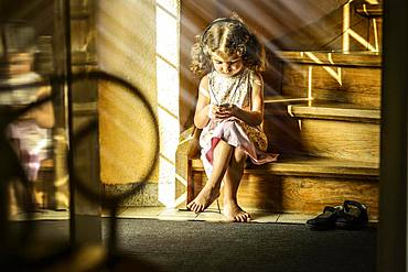 Girl, 3 years old, sitting on stairs listening to music with headphones, Germany, Europe