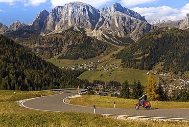 Motor scooter on winding road in autumn, Alta Batia, Hochabteital, autumn, Dolomites, South Tyrol, Italy, Europe