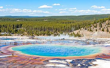 Visitors on footbridge over steaming hot spring with coloured mineral deposits, Grand Prismatic Spring, Midway Geyser Basin, Yellowstone National Park, Wyoming, USA, North America