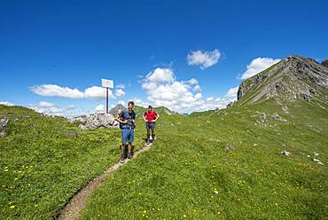 Two hikers on hiking trail Jubilaeumsweg at the Kirchdachsattel, sign state border, Allgaeuer Alps, Allgaeu, Bavaria, Germany, Europe