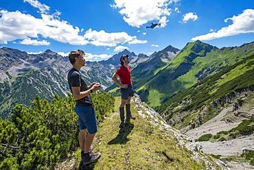 Two young men steer a drone, DJI Mavic, at the mountain top, at the back summit of the Hochvogel, hiking trail Jubilaeumsweg, Via Alpina, Allgaeu, Allgaeuer Hochalpen, Bavaria, Germany, Europe