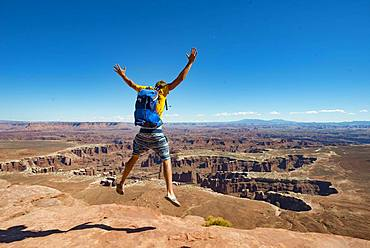 Young man jumping with outstretched arms, view from Grand Viewpoint, rugged gorges of the Green River, canyon landscape, erosion landscape, rock formations, Monument Basin, White Rim, Island in the Sky, Canyonlands National Park, Utah, USA, North America