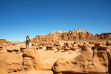 Tourist, young man likes Hodoo, eroded Hoodoos, rock formation of Entrada sandstone, Goblin Valley State Park, San Rafael Reef, Utah, southwest, USA, North America
