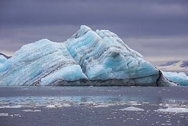 Floating chunk of ice before a huge glacier in Hornsund, Arctic, Svalbard, Norway, Europe