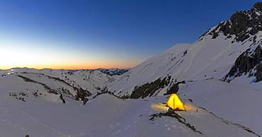 Illuminated tent in the snow on the Maedelejoch, dusk, near Kemptner hut, Allgaeuer Alps, Tyrol, Austria, Europe