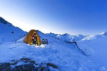 Snowshoe hiker in tent eating in the snow on the Maedelejoch, near Kemptner Huette, Allgaeuer Alps, Tyrol, Austria, Europe