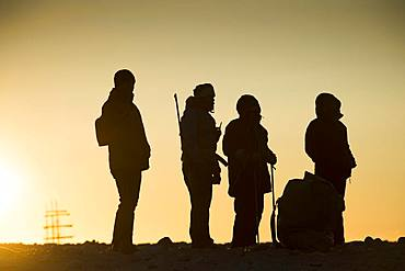 Tourists and tourist guides with rifle in backlight, silhouette, sunset, Kobbefjord, Spitsbergen archipelago, Svalbard and Jan Mayen, Norway, Europe