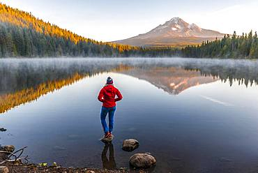 Young woman looking at view of volcano Mt. Hood with reflection in lake Trillium Lake, at sunrise, Oregon, USA, North America