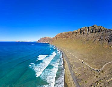 View on beach Playa Famara with mountain range Risco de Famara, at Caleta de Famara, behind island La Graciosa, drone shot, Lanzarote, Canary Islands, Spain, Europe