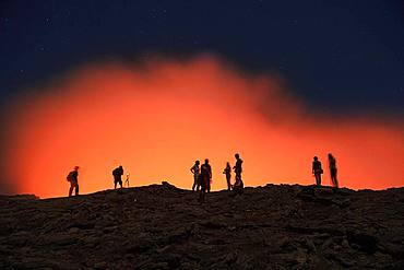 Tourists at the crater rim of the volcano Erta Ale in front of a red glowing steam cloud, Danakil Desert, Ethiopia, Africa
