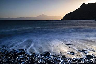 Sunrise at the beach Playa de Caleta, stones in the water, waves running out, view to Teide on Tenerife, La Gomera, Canary Islands, Spain, Europe