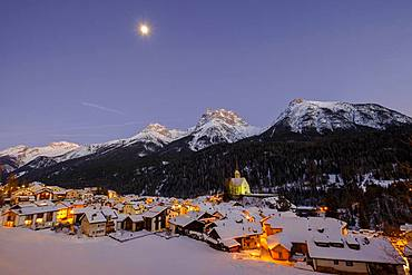 View of the town with Reformed church over the Inn in winter, dusk, Scuol, Graubuenden, Switzerland, Europe