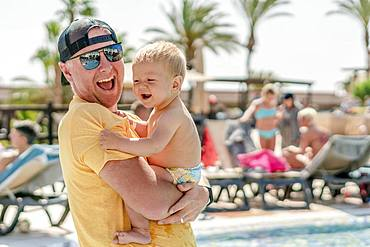 Happy father holding his cheerful son on holiday, resort with pool and palm trees as background, Portugal, Europe